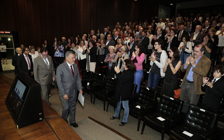 Tomaz Aroldo foi recebido de pé pela plateia e conduzido à mesa por um grupo de professores e técnicos-administrativos. Foto: Foca Lisboa/ UFMG